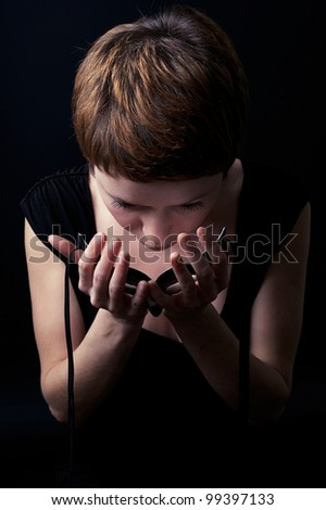 Surreal dark portrait of a young woman putting face mask on. - stock photo