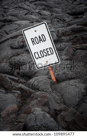 Surreal image of a road closed sign that has been partially covered from a lava flow - stock photo