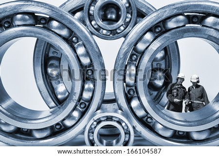 surreal industrial concept of workers standing inside giant ball-bearings - stock photo
