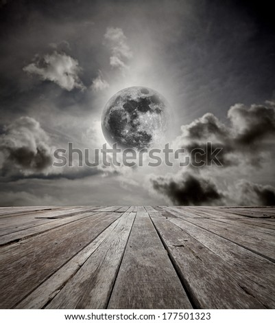 Surreal night sky with a full moon in the horizon of an empty grungy timber deck platform. Elements of this image furnished by NASA. - stock photo