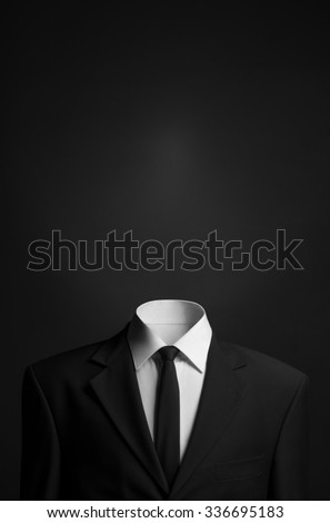 Surrealism and business theme: a man without a head in a black suit on a dark background in the studio - stock photo