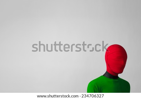 Surrealism Theme: a man in a green jacket with a red cloth tied around his head is in the corner on a gray background - stock photo