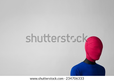 Surrealism Theme: man in a blue jacket with a pink cloth tied around his head is in the corner on a gray background - stock photo