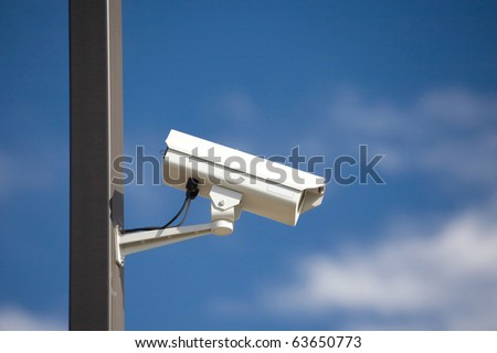 surveillance camera on light pole in parking lot - stock photo