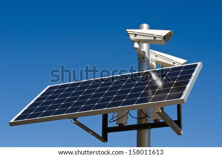surveillance camera with power from a solar panel - stock photo
