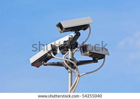 Surveillance cameras against blue sky - stock photo