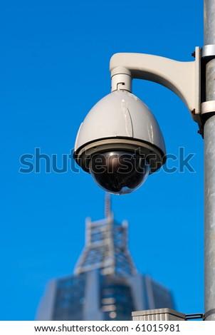 Surveillance Cameras of Office Building Under Blue Sky - stock photo