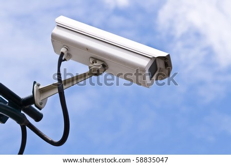 Surveillance Security Camera or CCTV on blue sky - stock photo