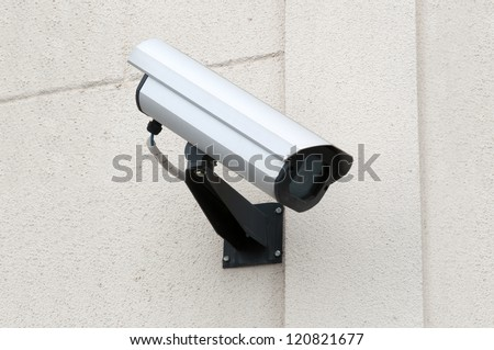 Surveillance security camera outside the building - stock photo