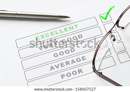 Survey form close up with tick on excellent - stock photo