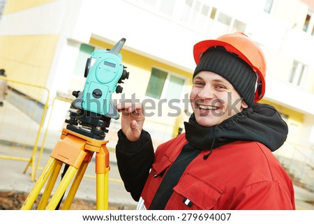 Surveying industry: smiling positive surveyor working with theodolite transit equipment at construction site  - stock photo