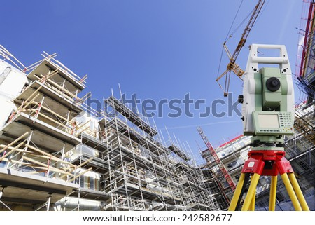 surveying instrument inside large construction site - stock photo