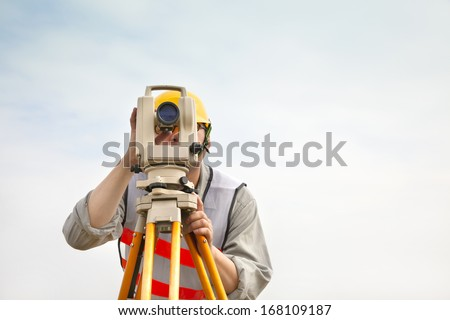 Surveyor engineer making measure with cloud background - stock photo