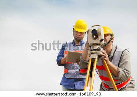 Surveyor engineer making measure with tablet pc - stock photo