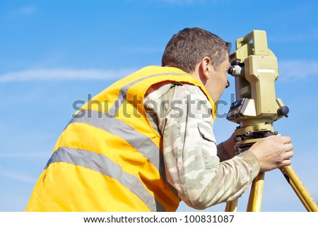 Surveyor engineer making measuring with optical equipment theodolite at blue sky background - stock photo