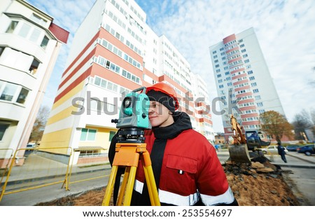 surveyor worker working with theodolite transit equipment at road construction site outdoors - stock photo