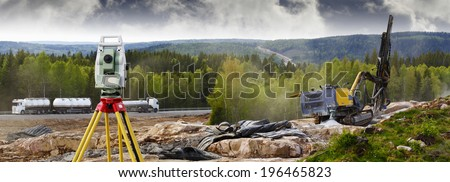 surveyors instrument measuring rock drilling for dynamiting, civil-engineering in action - stock photo
