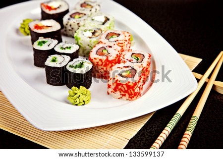 Sushi assortment served on white dish with wasabi and chopsticks - stock photo
