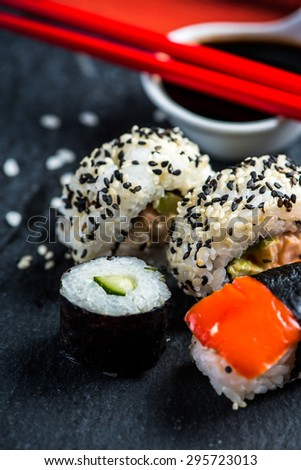 Sushi, chopsticks and wasabi, on black slate - stock photo