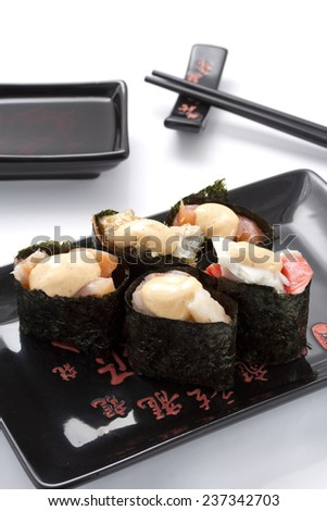 sushi gunkan in a black ceramic plate isolated on white - stock photo