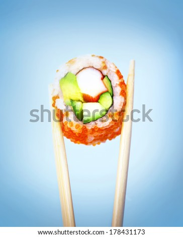 Sushi isolated on blue background, wooden chopsticks holding tasty fish roll, delicious food, exotic meal, traditional Japanese cuisine - stock photo