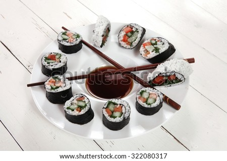 sushi maki rolls salmon with soy sauce and sticks on deep white plate on wooden table - stock photo