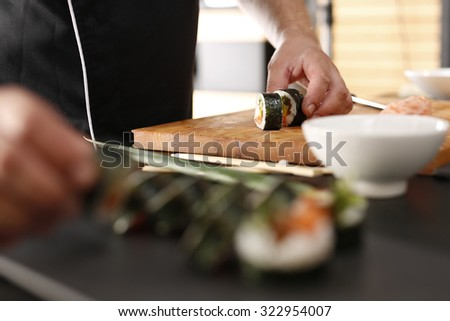 Sushi master preparing sushi in Japanese restaurant  - stock photo