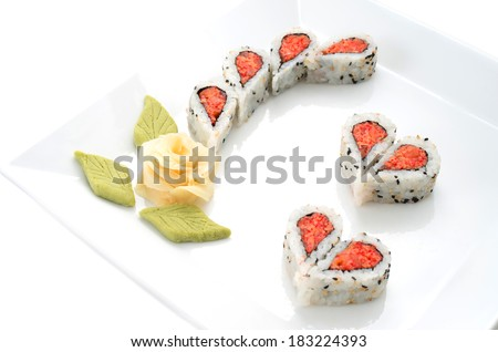 Sushi nicely decorated forming hearts  shapes on white square dish - stock photo