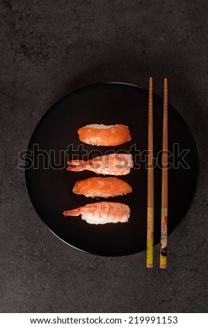Sushi nigiri assortment on black dish - stock photo