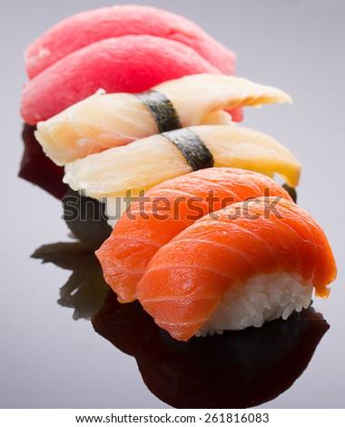 Sushi nigiri set on a stone plate over black background - stock photo
