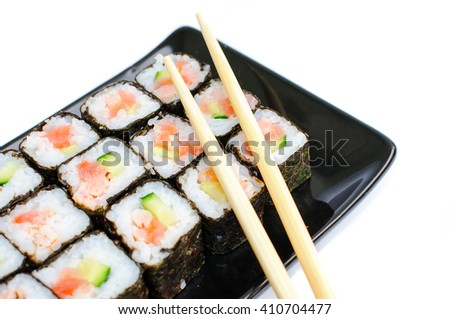 Sushi on a black plate with Japanese chopsticks it is isolated on a white background. - stock photo