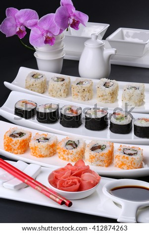 Sushi roll healthy food - japanese style. Various kinds served on white plate against the background of orchid - stock photo