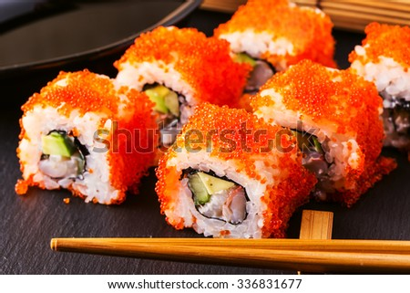 Sushi roll with crab, avocado, cucumber and tobiko, selective focus. - stock photo
