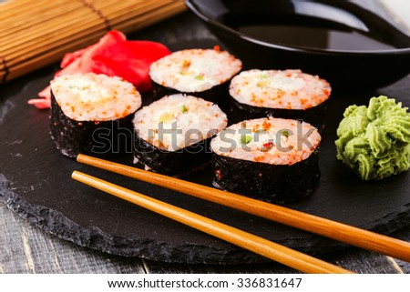 Sushi roll with crab, spicy sauce, cucumber and tobiko caviar, selective focus. - stock photo