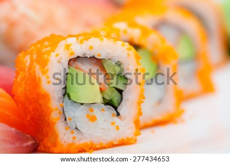 Sushi roll with salmon and shrimp tempura plate on a white background. - stock photo
