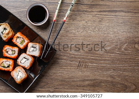 Sushi roll with salmon over wood background - stock photo