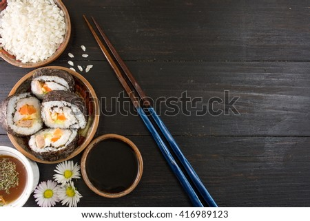 Sushi rolls and chopsticks with sushi ingredients - stock photo