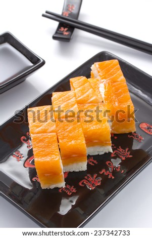 sushi rolls in a black ceramic plate isolated on white - stock photo