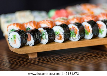 Sushi rolls served on a wooden plate in a restaurant - stock photo