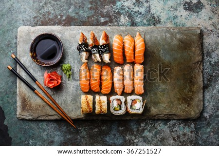 Sushi rolls set served on gray stone slate on metal background - stock photo