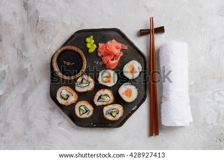 Sushi rolls set with marinated ginger, soy sauce and wasabi on stone background, selective focus - stock photo