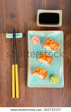 Sushi rolls with masago, served on turquoise plate with pickled ginger, soy sauce and chopsticks on wooden table. Aerial view.  - stock photo