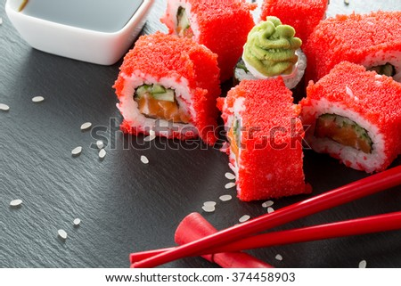 sushi rolls with red chopsticks and sauce on a slate table - stock photo