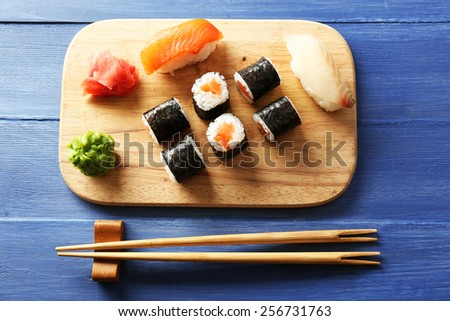 Sushi rolls with salmon on tray, on wooden background - stock photo