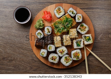 Sushi set at round wooden plate on wooden table - stock photo
