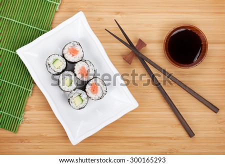 Sushi set, chopsticks and soy sauce over bamboo table - stock photo