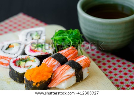 Sushi Set in wooden dish with tea cup - stock photo