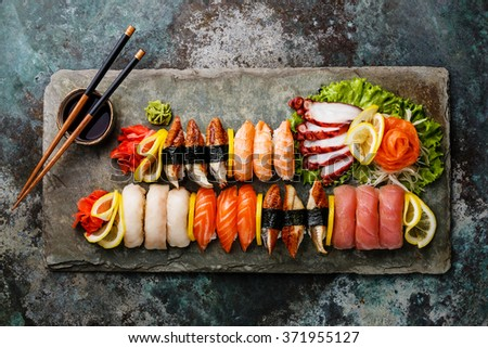 Sushi Set nigiri and sashimi served on stone slate background - stock photo