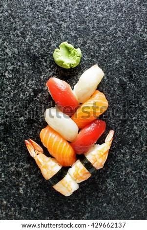 Sushi Set nigiri served on black marble slat. Christmas tree in the Japanese style - stock photo