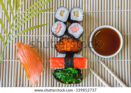 Sushi set on bamboo table with soy sauce - stock photo